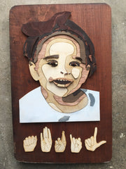 """Wooden layered/lines picture of one year old Latinx girl with handshapes """"ABRIL"""" at the bottom"""