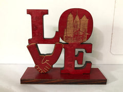 "Wooden stand of ""LOVE"" on base with engraved ""CEASED 2020"""