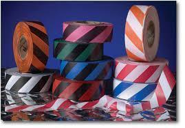 Several rolls of striped flagging tape, with various colours. Displayed against a blue background.