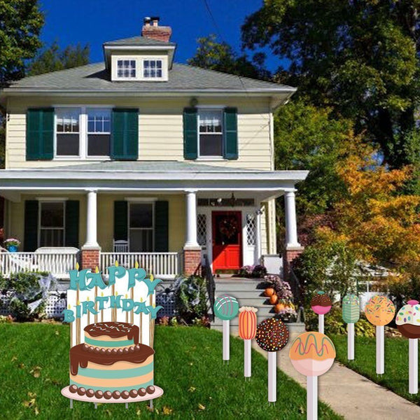 A front yard with a cake yard decoration sign with yard decoration pathway markers