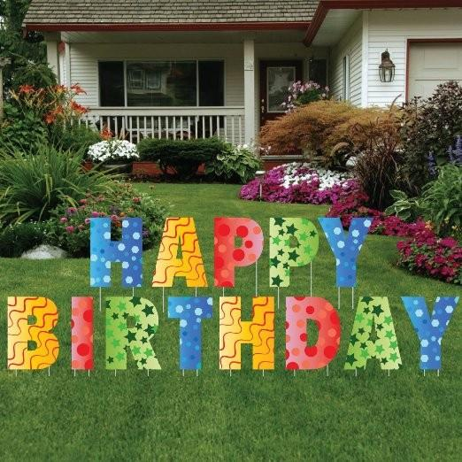 The front yard of a house with yard decoration that spell Happy Birthday