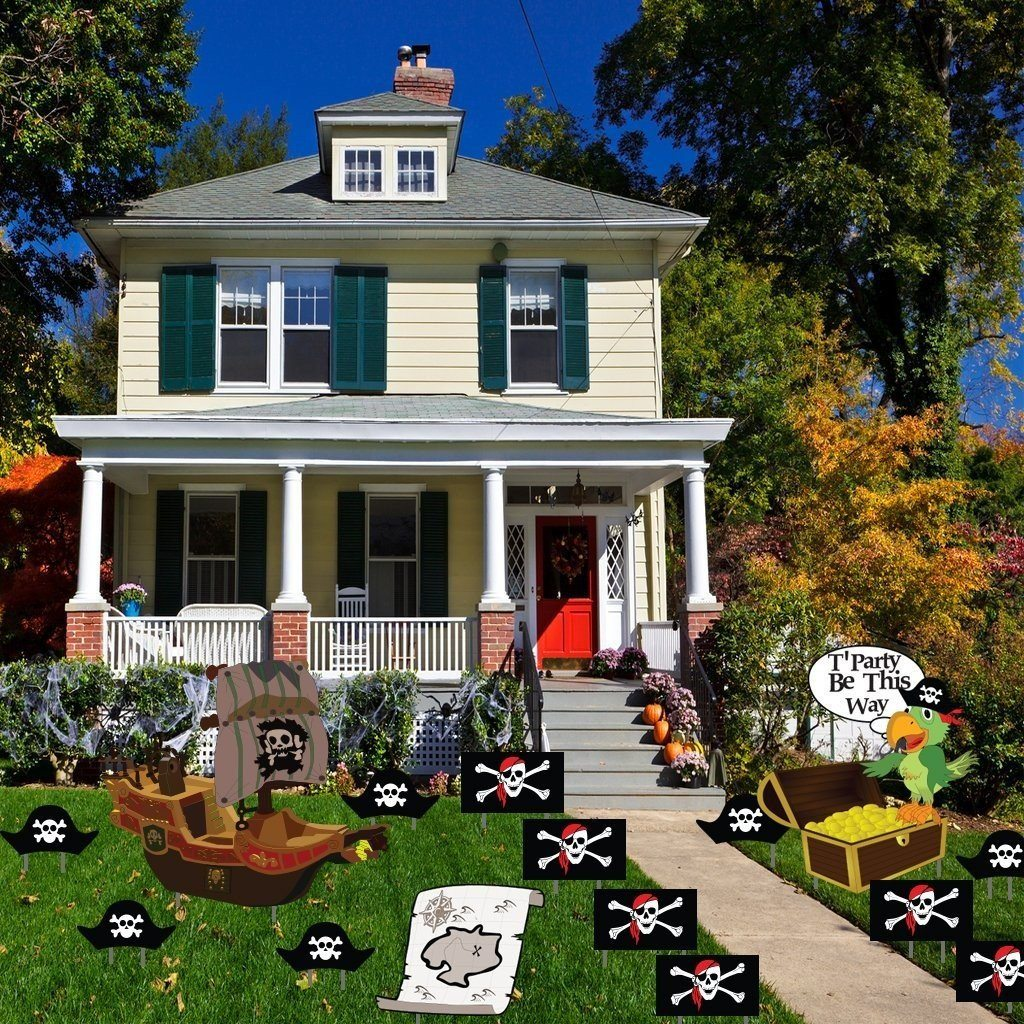 The front yard of a house with several pirate themed birthday yard decorations