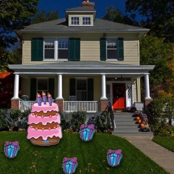 The front yard of a house with a large birthday cake with small presents
