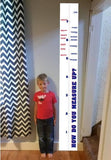 A kid standing next to a sports themed growth chart