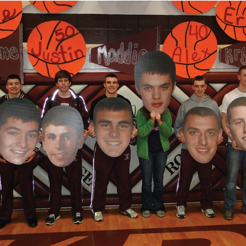 several big head cutouts of students