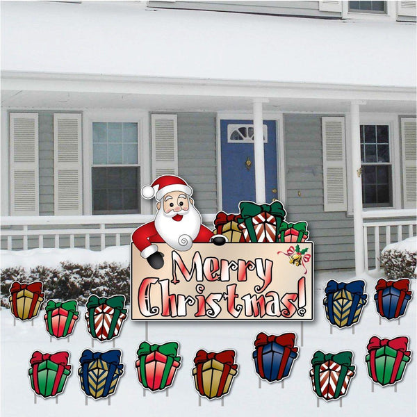 The front yard of a house with a collection of Christmas decorations including Santa and several presents