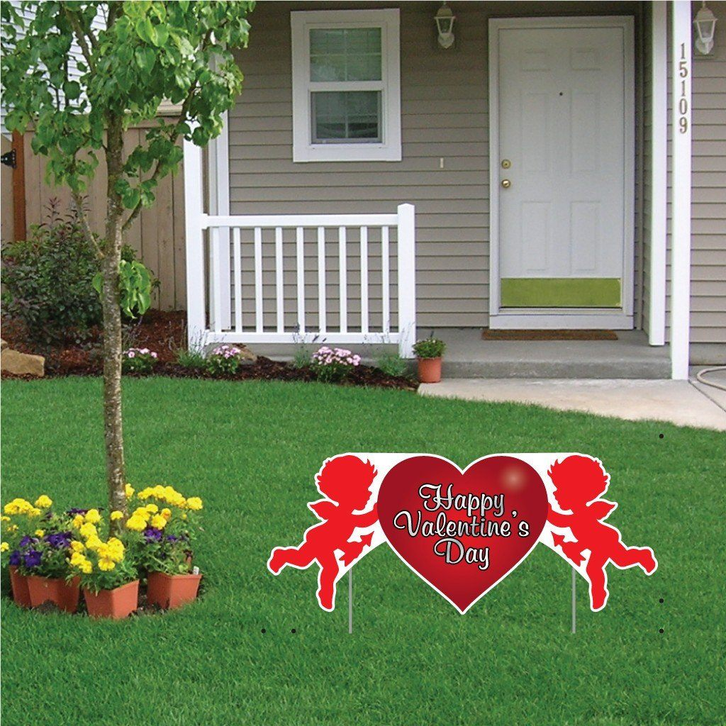 The front yard of a house with a valentine's day yard decoration in it