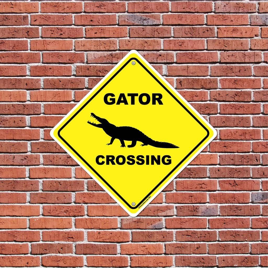 "A yard sign that says ""Gator Crossing"" on a brick wall"