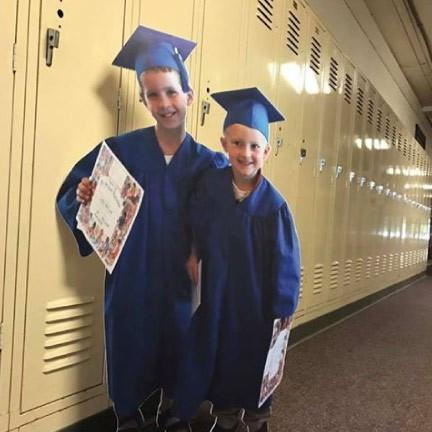 A cutout of two kids that are graduating