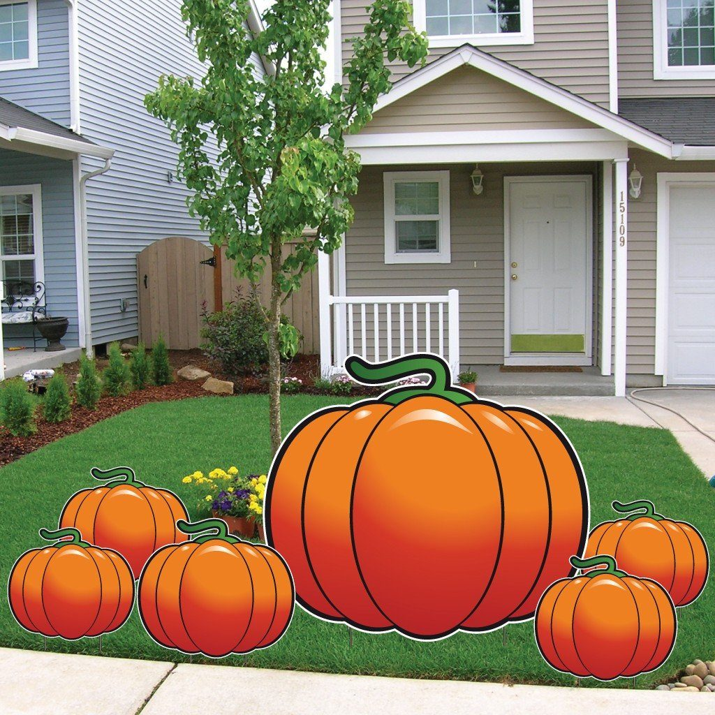 Front yard of a house with 1 large pumpkin cut-out with 5 mini pumpkin cut-outs