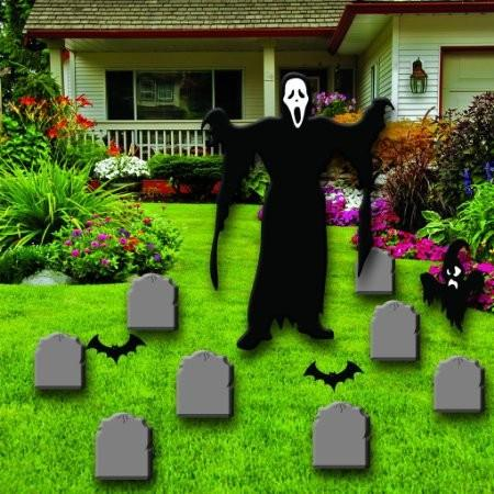 The front yard of a house with 8 tombstone cutouts and a large ghoul cut out