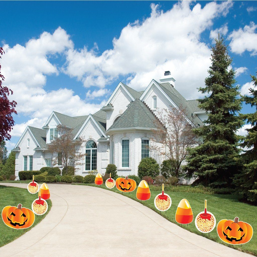 The front yard of a house with 12 pumpkin yard decoration lining a driveway