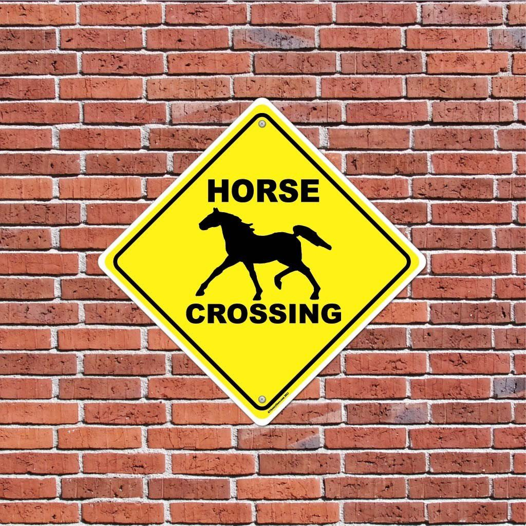 A horse crossing sign on a brick wall