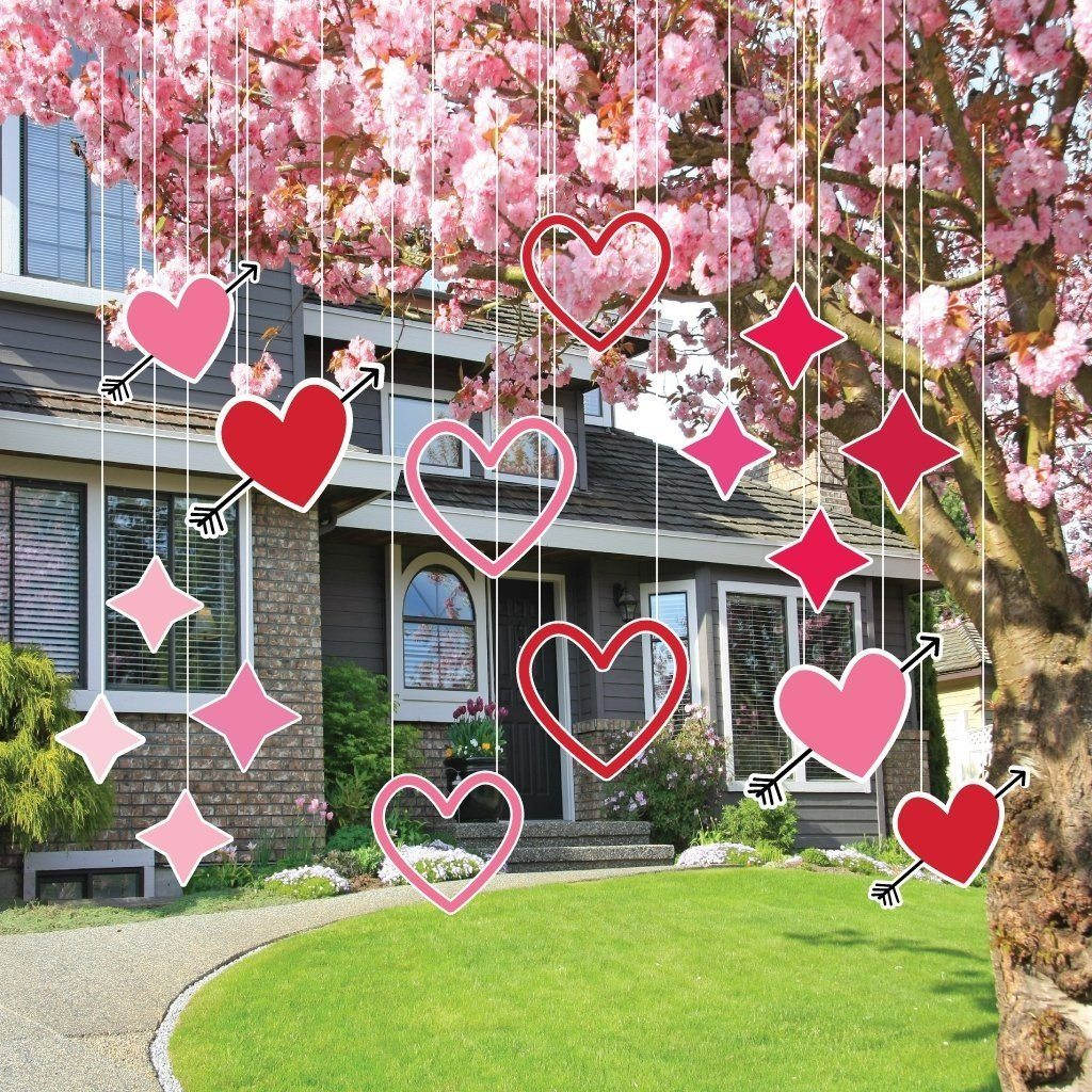 Valentines day yard decorations hanging from a tree