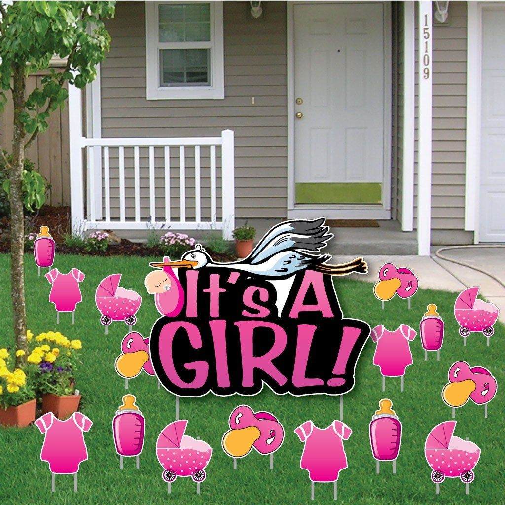 A yard with several signs celebrating a gender reveal
