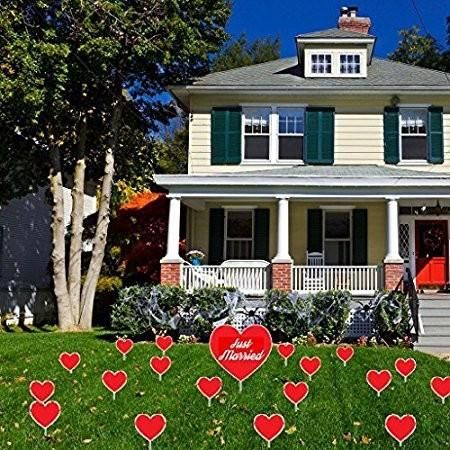 The front yard of a house with several red hearts for a married couple