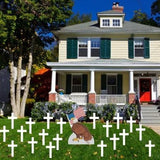 The front yard of a house with a eagle holding an American flag with several Crosses surrounding him