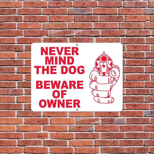 A beware of owner sign on a brick wall