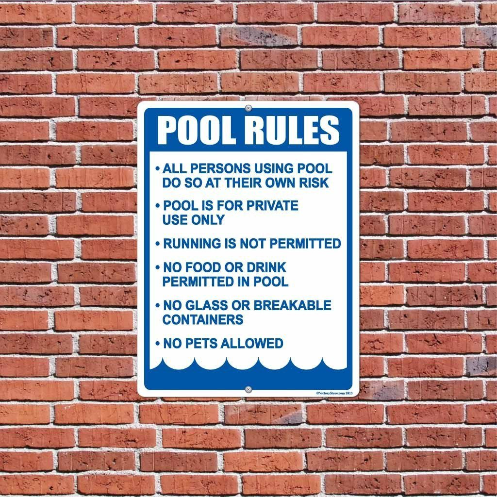 A yard sign that has pool rules on it