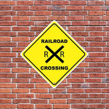 A railroad crossing sign on a brick wall