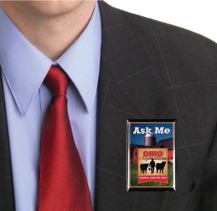 A man in a suit with a personalized button