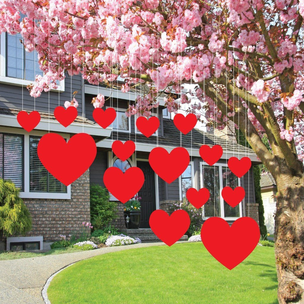 The front yard of a house with several Valentine's day hearts hanging from a tree