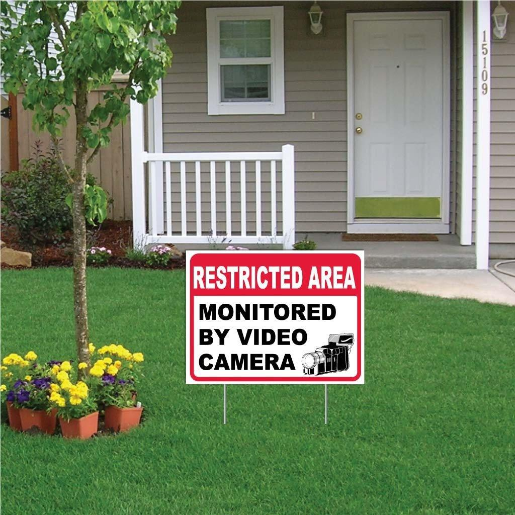 "A yard sign that says ""Restricted area monitored by video camera"