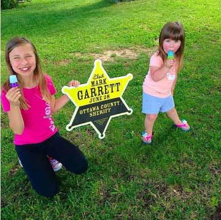 two girls standing next to a custom printed yard sign