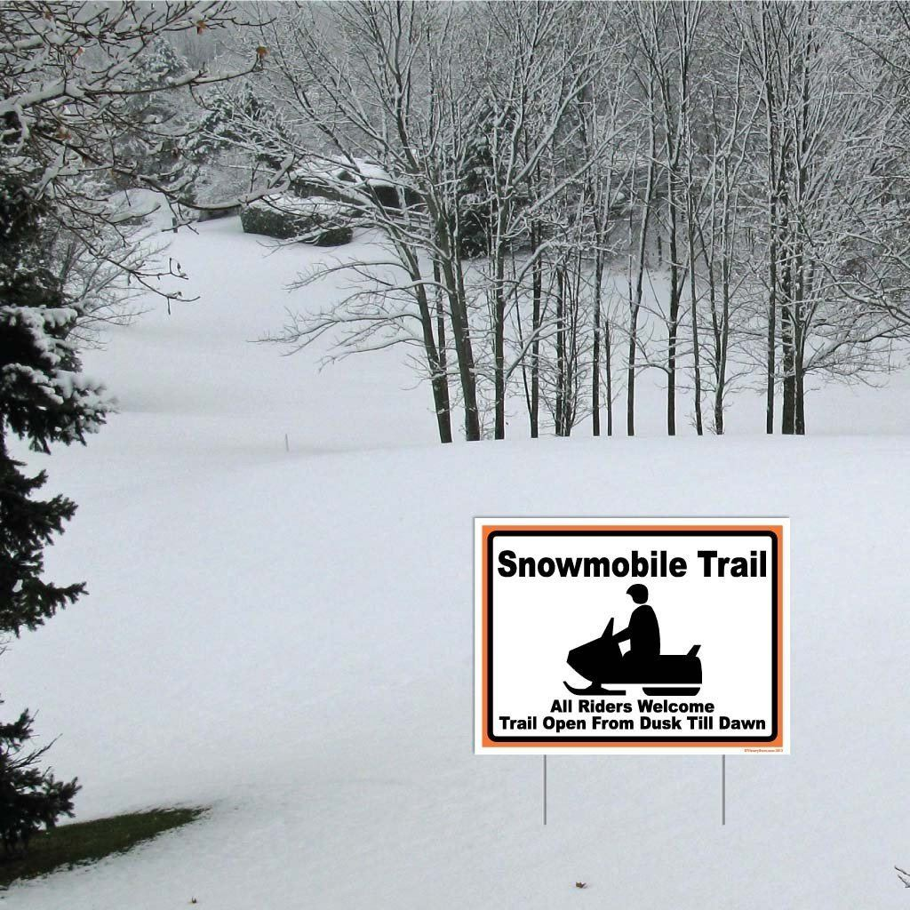 "A yard sign that says ""Snowmobile Trail all Riders Welcome Trail Open From Dusk Till Dawn"""