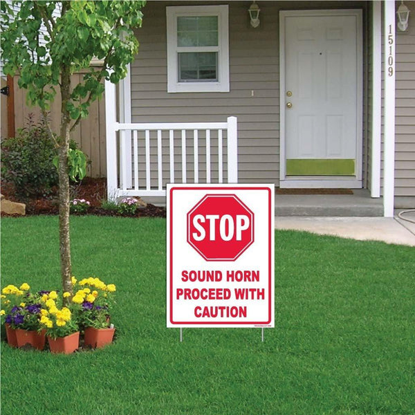 "A yard sign that says ""Stop, sound horn proceed with caution"""