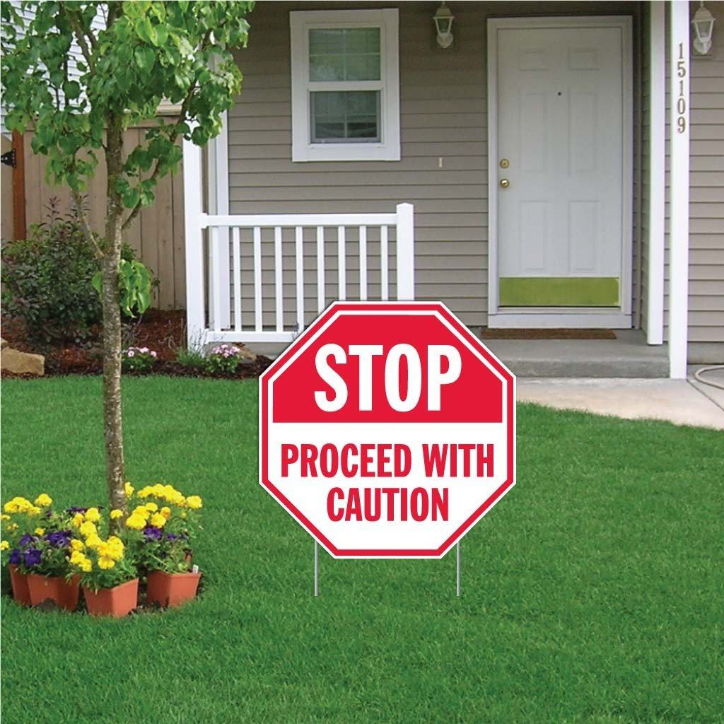 "A yard sign that says ""Stop, Proceed with caution"""