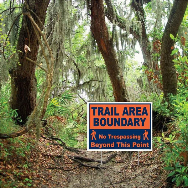 "A yard sign that says ""Trail area boundary, no trespassing beyond this point"""