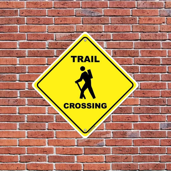 A trail crossing sign on a brick wall
