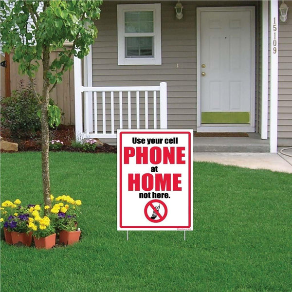 "A yard sign that says ""Use your cell phone at home, not here."""
