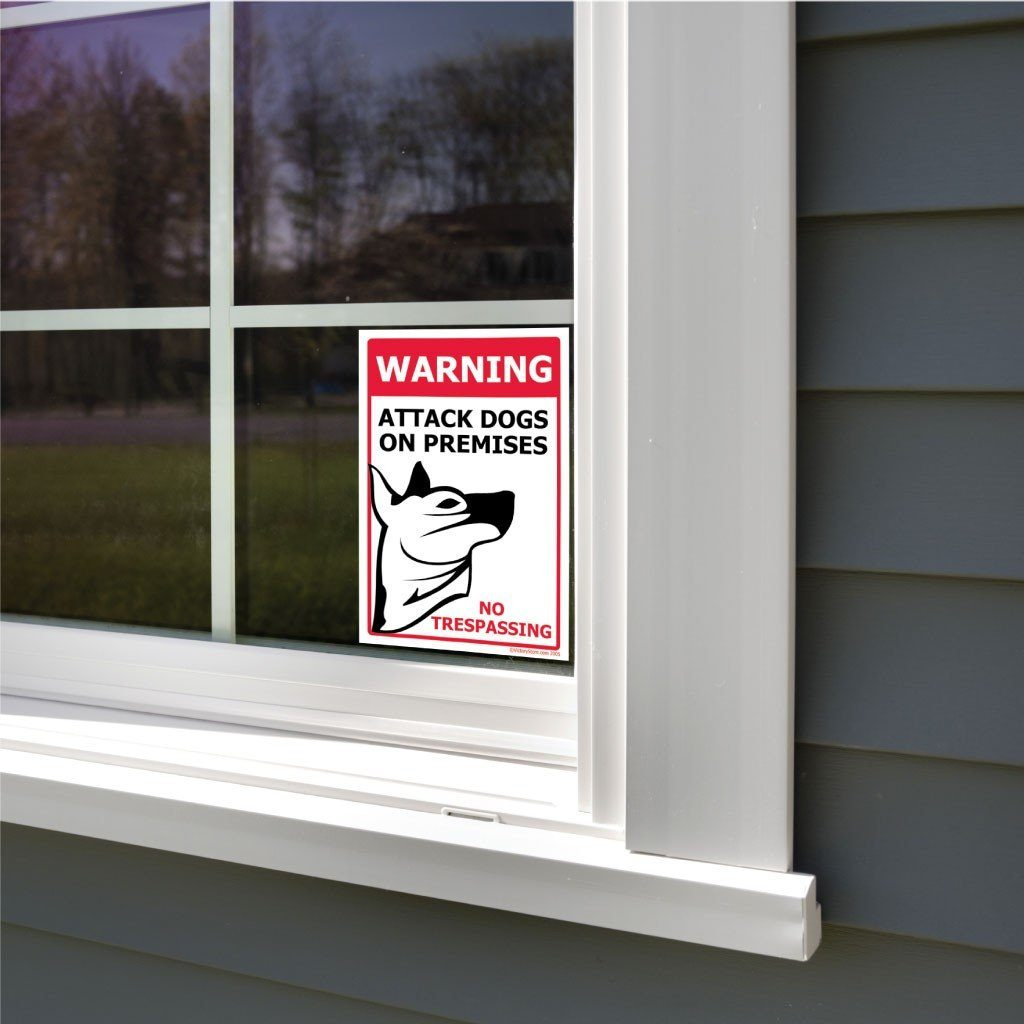 A beware of dog sticker attached to a window