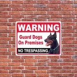 A warning sign for an attack dog on a brick wall