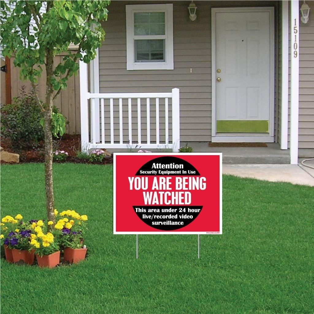 "A yard sign that says ""You are being watched"""