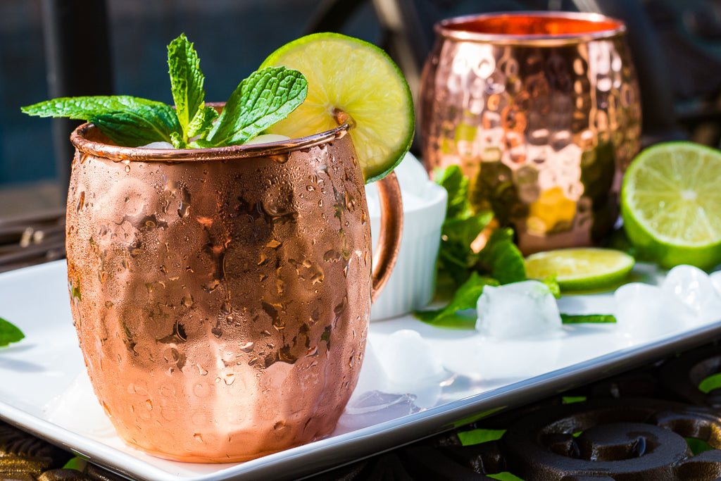 Moscow Mule Cocktail With Lime Rim and Mint On White Tray Outdoors with Copper Mugs by Urban Vintage LA