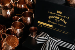 Artisanal Set of 4 Moscow Mule Copper Mugs Next to Black Gift Box and Gift Wrapped Box with Faux Lizard Leather Paper and Black and White Ribbon