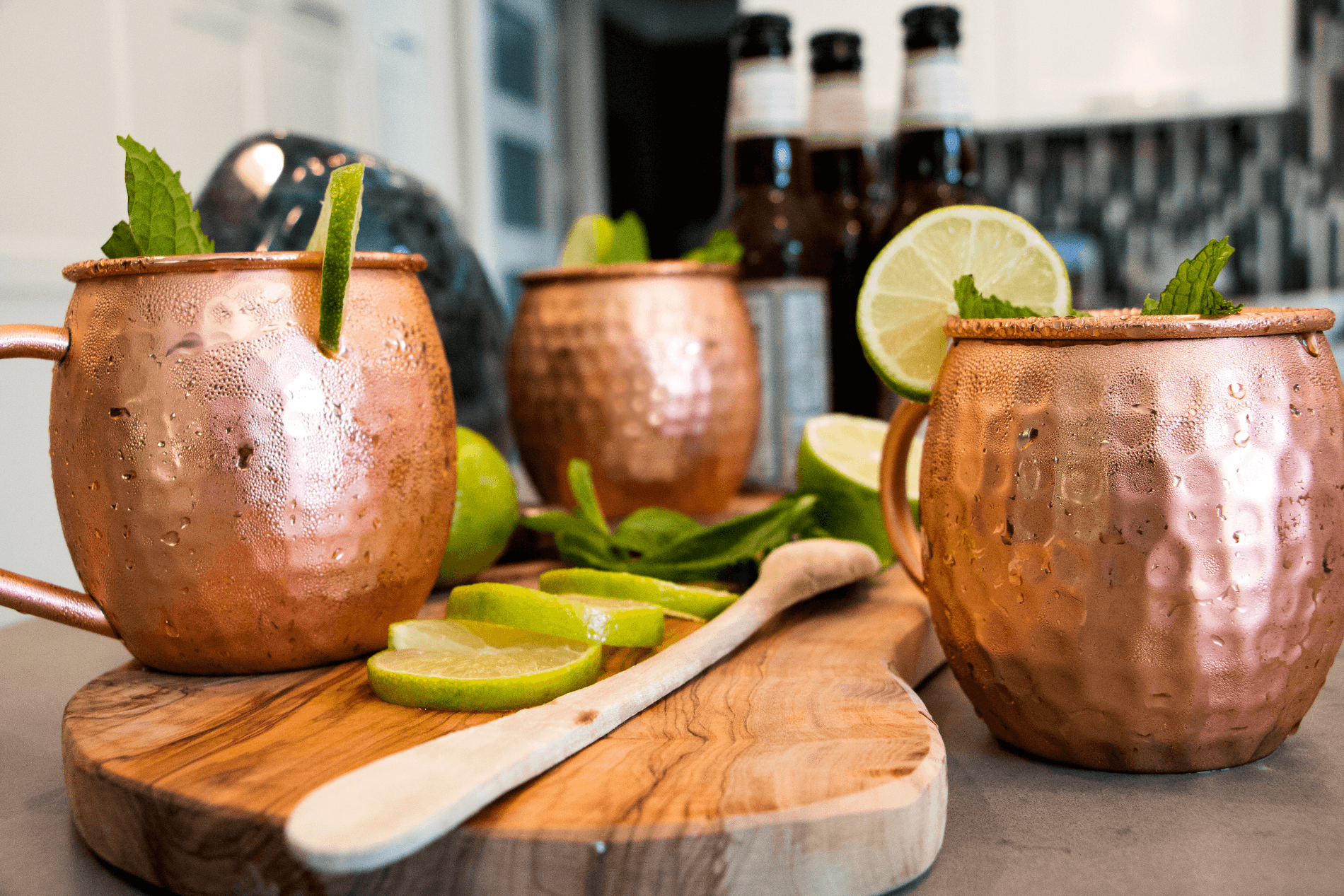 Preparation of Moscow Mule Cocktail With Urban Vintage LA Copper Mugs On Cutting Board With Limes And Mint