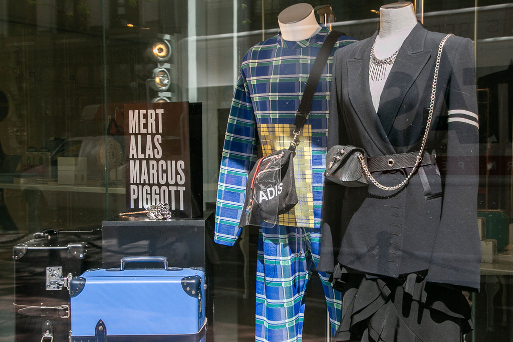Luxurious fashion clothing with bags, luggage, platinum rose, on a window display at Secret Location concept store