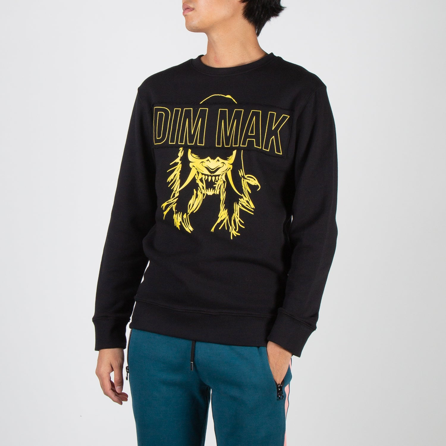 Yellow Demon Mask design on black pullover sweater by Dim Mak at Secret Location