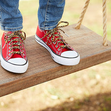 leopard print shoelaces standing on a tree swing