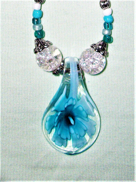 Blue necklace with a blue flower pendant.
