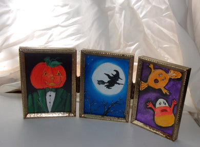 triptych Halloween themed miniature art works of a pumpkin head man a witch and scared candy