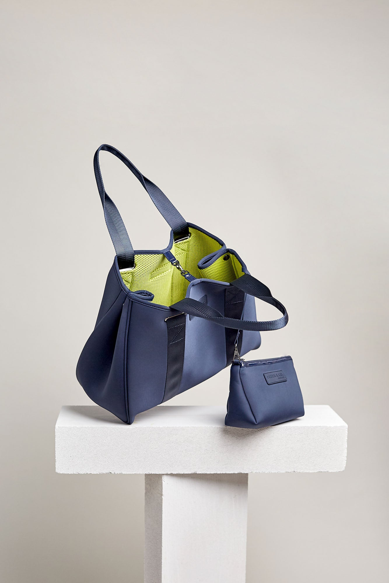 Dark blue neoprene and neon yellow mesh tote bag. Luxury sport and travel style bags