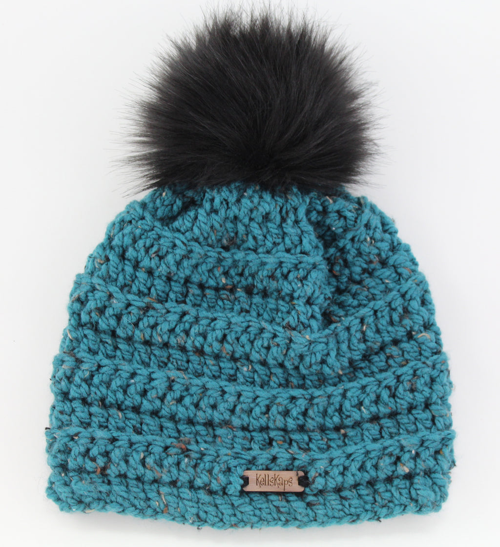 The Kells Beanie in Teal Tweed with a Black Faux Fur Pom