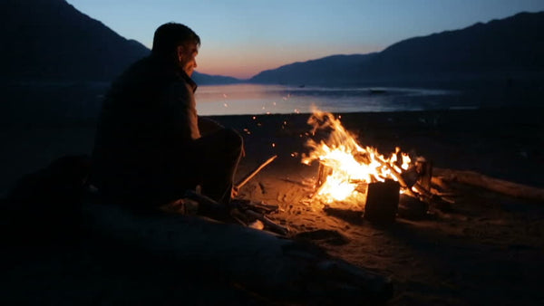 Man sitting on a beach by an open campfire