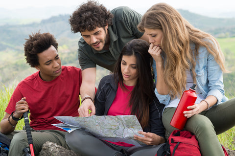 Multicultural group of people looking at a map with landscape background