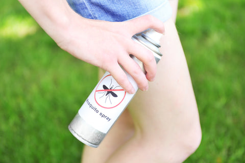 Woman spraying insect repellent outdoors